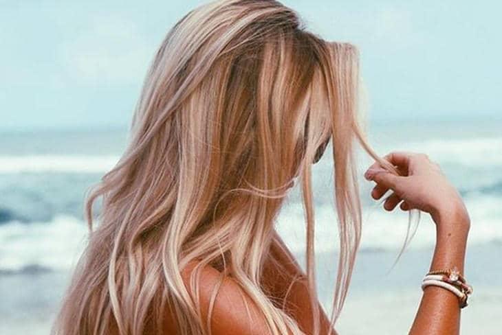 chica con el pelo aclarado en la playa soleada y su difuminador solar en el cabello